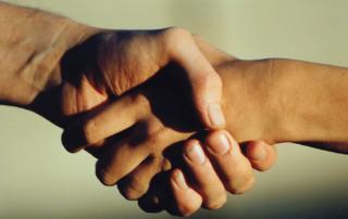 Na zdjęciu dwie ściskające się dłonie w geście gratulacji lub powitania.