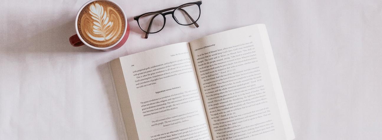Na zdjęciu widoczna jest książka, okulary i filiżanka kawy na białym tle
