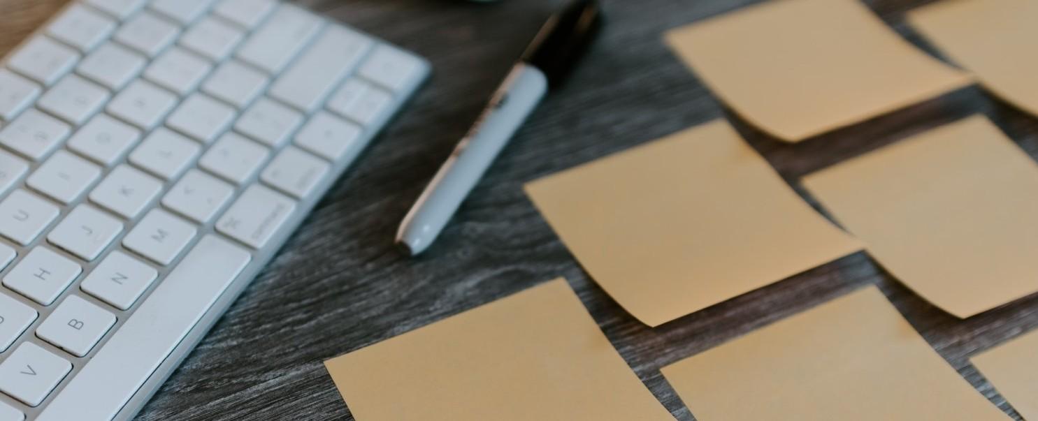 Zdjęcie przedstawia ciemne biurko, na którym leżą biała klawiatura, pisak oraz żółte małe karteczki do notowania pomysłów