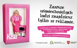 """Grafika przedstawia białe tło, na którym po lewej stronie znajduje się różowy karton przypominający opakowanie od lalki oraz ustylizowaną na lalkę wewnątrz kartonu aktorkę Kasię Bujakiewicz, która nienaturalnie się uśmiecha. Po prawej stronie znajduje się czarny napis: """"Zawsze uśmiechniętych ludzi znajdziesz tylko w reklamie"""". Pod tym sloganem znajduje się drugi napis w kolorze białym na różowym tle: """"Dowiedz się, jak zadbać o zdrowie psychiczne w prawdziwym życiu i gdzie szukać pomocy w razie kryzysu. Wejdź na www.rops.poznan.pl"""". Pod napisami znajduje się hasło kampanii #PrawdziwiLudzie oraz dwa logotypy: Regionalnego Ośrodka Polityki Społecznej w Poznaniu oraz Samorządu Województwa Wielkopolskiego"""