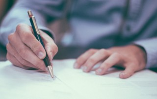 Na zdjęciu widoczny zarys sylwetki mężczyzny, który opisuje dokumenty leżące na biurku