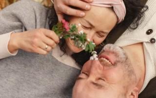 Na zdjęciu seniorzy leżący na trawie. Przytulają się i wąchają kwiaty