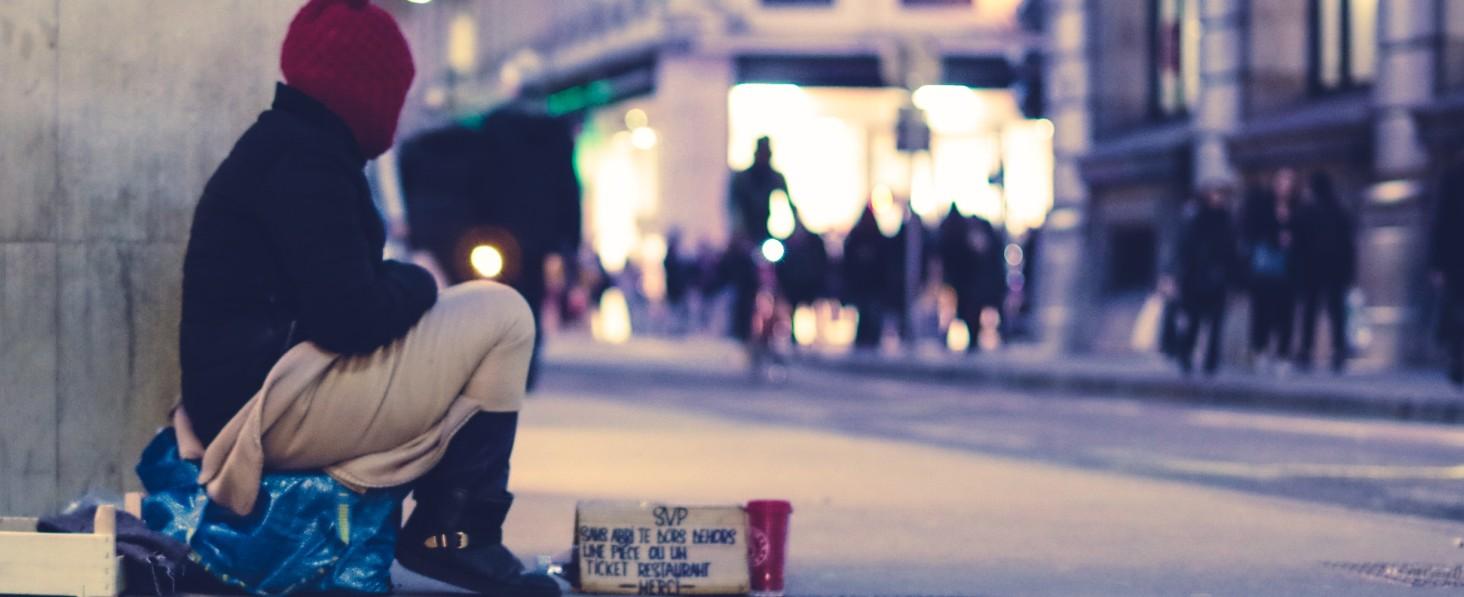 Na zdjęciu widoczna jest osoba bezdomna na ulicy zbierająca pieniądze