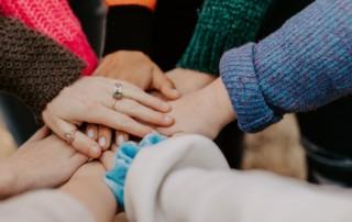 Na zdjęciu widoczne są położone dłonie jedna na drugiej oznaczające solidarność i współpracę