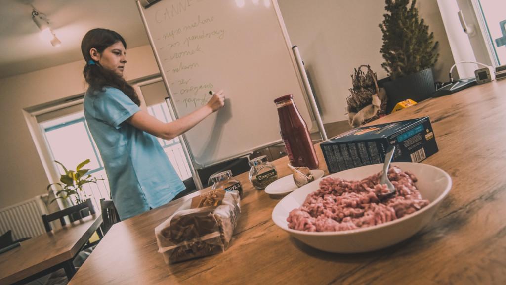 Zdjęcie przedstawia dziewczynę, która zapisuje na tablicy składniki na danie obiadowe. Na stole znajduje się mięso mielone w misce, sos pomidorowy w butelce, makaron, czosnek, ser i przyprawy.