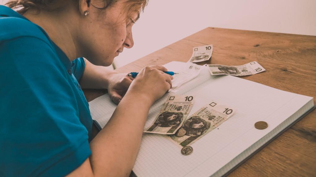 Zdjęcie przedstawia osobę siedzącą przy stole i liczącą pieniądze. Na stole znajdują się banknoty, monety oraz zeszyt, w którym osoba zapisuje obliczenia.