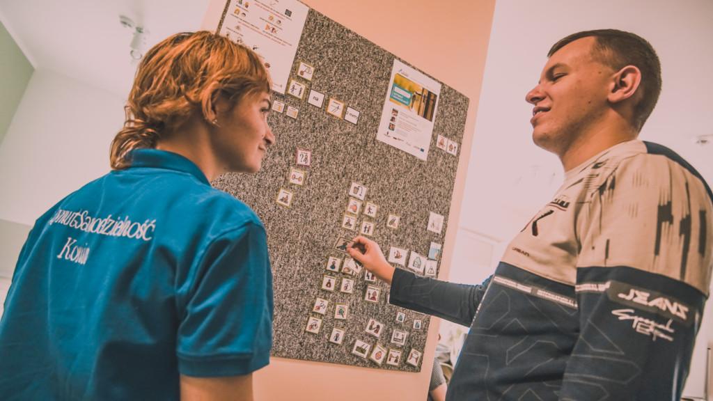 Zdjęcie przedstawia dwie osoby stojące przy tablicy. Osoby patrzą na siebie i uśmiechają się.