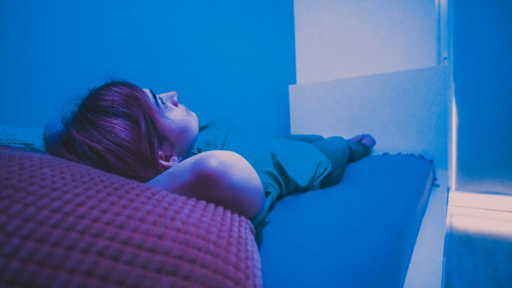 Zdjęcie przedstawia osobę leżącą na łóżku. Ręce trzyma pod głową. Patrzy na sufit. Niebieska kolorystyka.