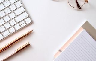 Zdjęcie przedstawia biurko, na którym znajdują się: okulary, notatnik, przybory do pisania, widoczny jest fragment klawiatury komputera.