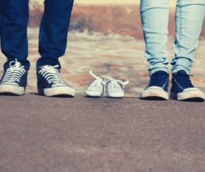 Zdjęcie przedstawia nogi osób, od kolan w dół. Pomiędzy nimi znajdują się puste buty dziecięce.
