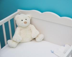 Na zdjęciu łóżeczko dziecięce, w którym siedzi pluszowy miś.