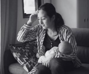 Czarno-biała fotografia, która przedstawia kobietę trzymającą dziecko.